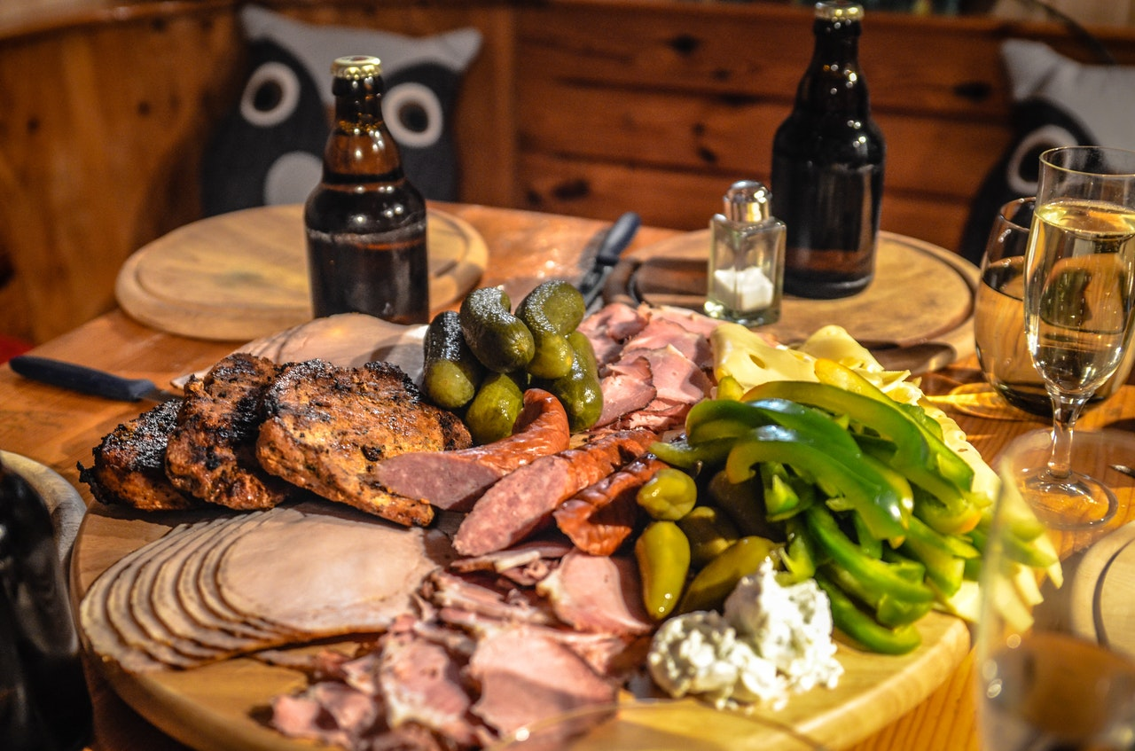 Prostřený stůl-dvě láhve s pivem, tác obložený masem, klobásami a zeleninou